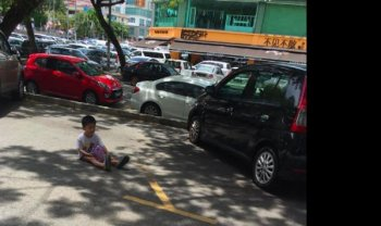 Bắt con ngồi giữa khu đỗ xe để… giữ chỗ